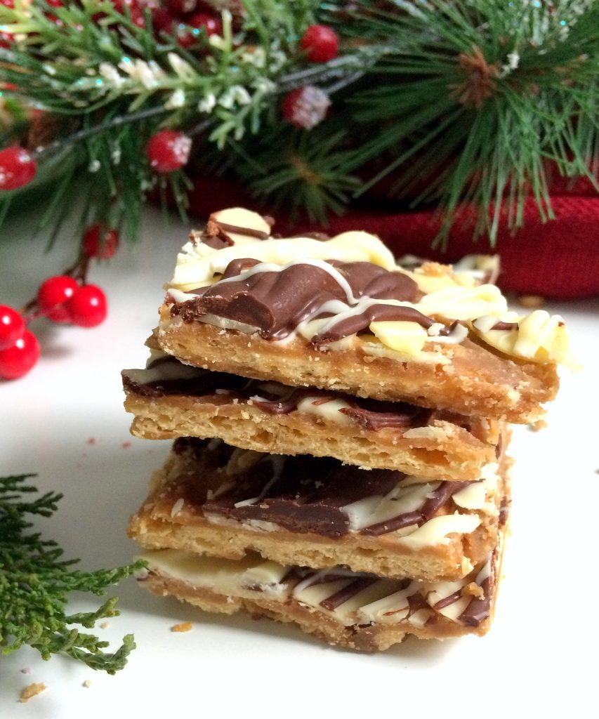 Make this easy almond roca recipe for your Christmas and Holiday baking and watch it disappear. There's a good reason they call it Christmas Crack! This variation uses saltines, brown sugar, butter, almonds, milk chocolate and white chocolate. #christmasbaking #holidaybaking #almondroca #christmascrack #ppholiday #easy #dessert #squares