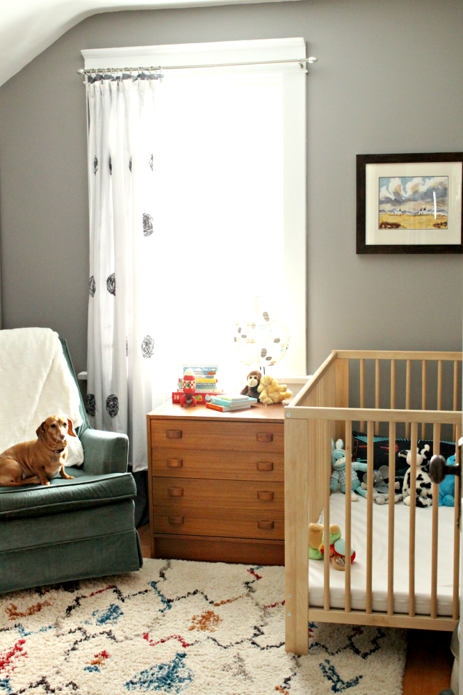 Don't you love this gender neutral nursery? Perfect for a baby boy or girl, and easy to transition to the next child. I love the white, red, and blue shag rug, and how it perfectly compliments the retro blue chair. #genderneutralnursery #boysnursery #girlsnursery