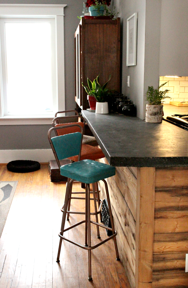 Vintage bar stools in turquoise, orange, and brow. I love how the retro stools contrast with the concrete countertops and reclaimed wood. #vintage #retro #barstools #concretecountertop #reclaimedwood