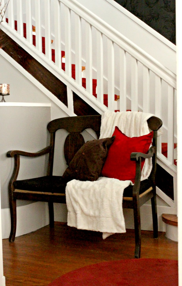 I love this wooden bench in the entryway. Such a lovely contrast with the white, grey, black, and pop of red. So cosy and inviting! #characterhome, #popsofcolor #entryway #stairway