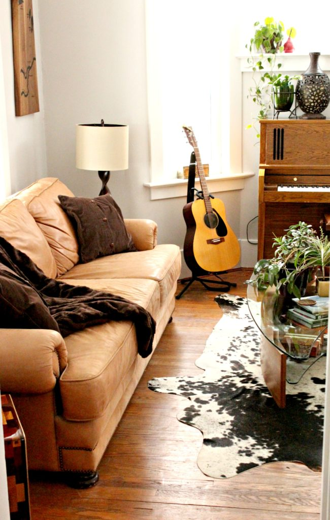Let's curl up on this cozy brown leather couch and listen to some music. Don't you want this in your music room? #livingroom #musicroom #brownleathercouch #leathercouch #piano #guitar