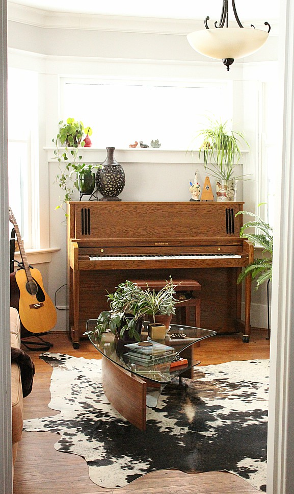 Calling all music lovers and crazy plant ladies! This is the perfect living room for you. I'm so jealous of all the natural light and the gorgeous cowhide rug. #musicroom #livingroom #crazyplantlady #cowhiderug #uprightpiano