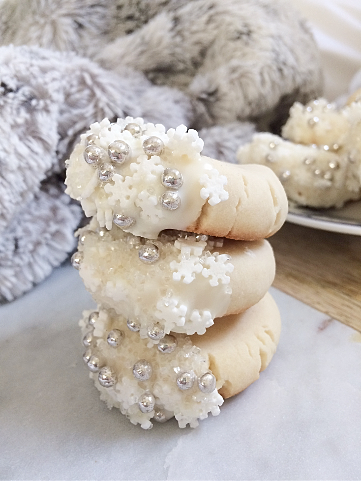Your Christmas cookie exchange isn't complete without these easy, melt-in-your-mouth shortbread cookies dipped in white chocolate and snowflake sprinkles. Make a double batch, because the soft and buttery taste will have everybody coming back for more! #shortbread #cookies #Christmas #baking