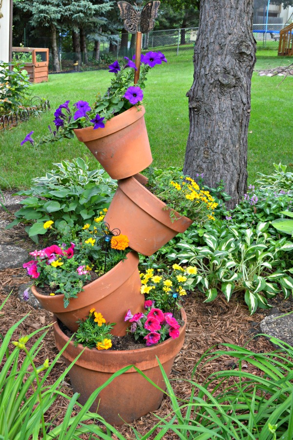 I think whimsical garden art really makes a backyard flower bed.  I love these 20 diy ideas that are either recylcled, upcylcled, or from junk that nobody wants.  I need to do some of these in my outdoor space--these tipsy garden pots are just the cutest! #gardenart #whimsical #flowergarden #landscapingideas