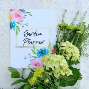 Garden planner with light green and cream flowers beside it.